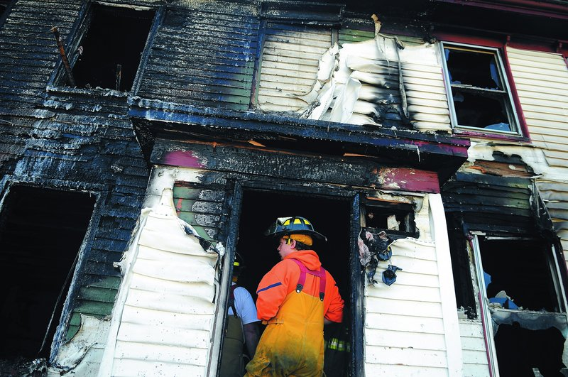 Firefighters inspect the interior of an apartment building that burned Saturday night and Sunday morning on Route 226 in Randolph. The blaze is under investigation by authorities.