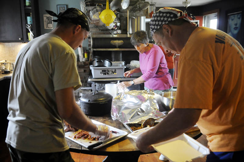 HELPING HANDS: Volunteers Heath Schwab, left, Kathy Walley and Stephen Dodge, right, prepare meals Wednesday in the kitchen of Annabessacook Farm in Winthrop. Volunteers prepare meals with local produce to feed the hungry at the farm.