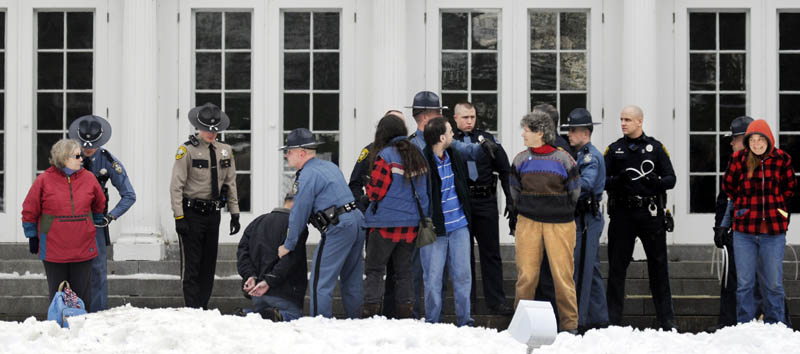 CUFFED: Protesters are arrested Sunday on the lawn of the Blaine House during a rally by Occupy Augusta.