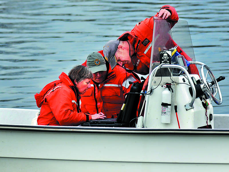 "STURGEON HUNTERS: Maine Department of Marine Resources biologists Gail Wipplehauser, left, Jason Valliere and Jason Bartlett search for SNAP Monday on a computer they used to track the fish with a sonar while floating on the Kennebec River between Gardiner and Randolph. The scientists were hoping to determine why the shortnose and Atlantic sturgeon tagged with transmitters had not migrated to their winter terrain in the Kennebec River in Richmond, according to Wipplehauser. ""They seem to be roaming this year,"" she said of fish that reach up to nine feet in size. The sonar study of shortnose, an endangered species, and Atlantic sturgeon is funded by the National Oceanic Atmospheric Administration, a federal agency."