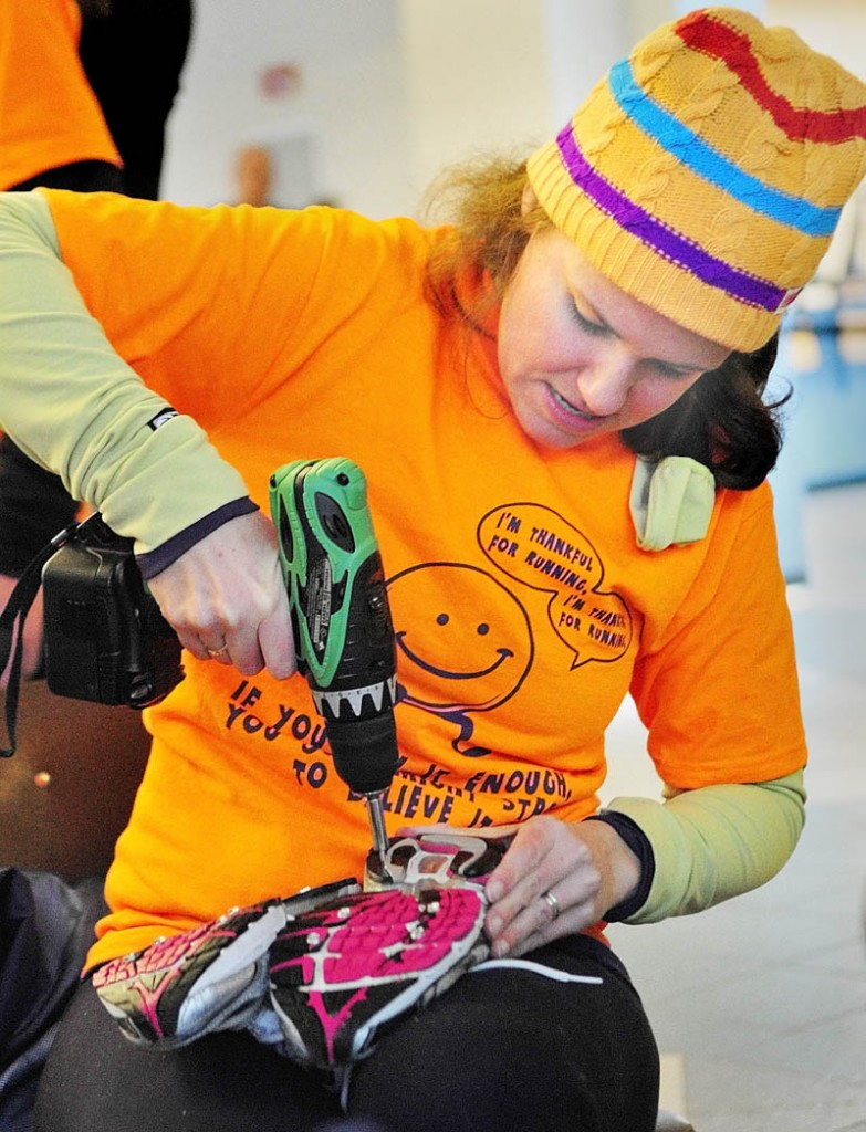 Amy Lawson drives 3/8 inch sheet metal screws into a teammate's running shoes on Thursday morning before the Gasping Gobbler 5K Road Race to Benefit Cony High School Athletics in Augusta. The screws are short enough that they don't go through the shoes and the heads give traction like studded snow tires on the icy roads.