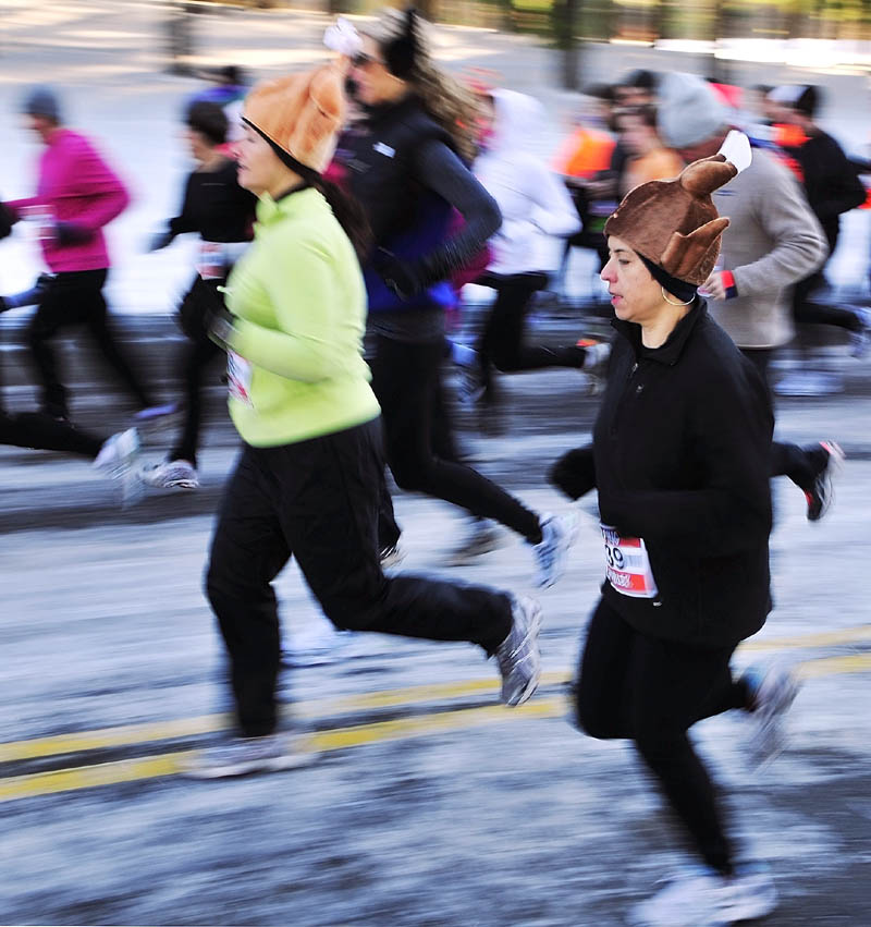 Laura Gosselin, left, and Sarah McGuire, both of South China, wear turkey hats on Thursday morning as they start the Gasping Gobbler 5K Road Race to benefit Cony High School athletics in Augusta