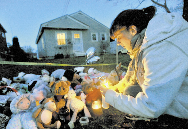 TRIBUTE: Tara True, of Winslow, lights candles at the ever growing teddy bear shrine in front of missing 20-month-old Ayla Reynolds' Waterville home on Wednesday.