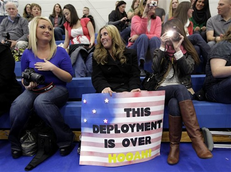 Brittney Davis, center, waits for her husband, U.S. Army Sgt. Donald Davis, Tuesday, Dec. 6, 2011, as she sits with Whitney Joy, left, who was waiting for her husband, Staff Sgt. Alex Joy, and their friend and personal photographer, Arielle Peace, right, as they wait for a welcome home ceremony to begin at Joint Base Lewis McChord in Washington state for soldiers who had been serving in Iraq. (AP Photo/Ted S. Warren)