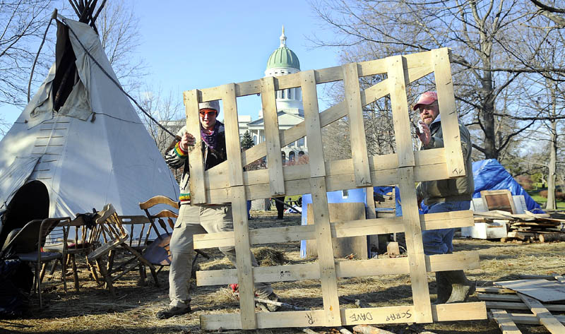Occupy Augusta participant Lew Kingsbury, right, and Nick Messier carry a tent platform Thursday from Capitol Park in Augusta.