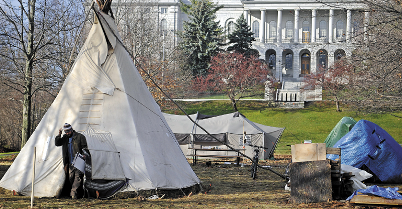 RISE AND SHINE: An Occupy Augusta movement member emerges from a teepee Wednesday morning at Capitol Park in Augusta. Approximately six people slept overnight in the park in tents and a teepee while the future of the protest will be determined in federal court.