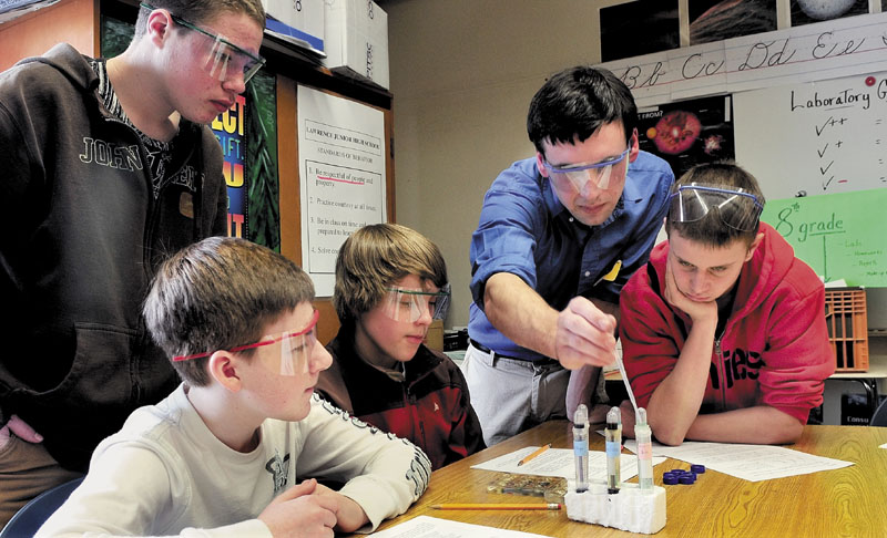 GOOD CHEMISTRY: Colby College student Ben Bricker assists Lawrence Junior High School students during a science exercise on Tuesday. From left are Max Davidson, Alex Hayes, Iyan Blaisdell, Bricker and Jacob Dickson. Bricker and fellow student Teko Mmolawa are enrolled in a college program designed to offer student-initiated academic programs under faculty supervision.