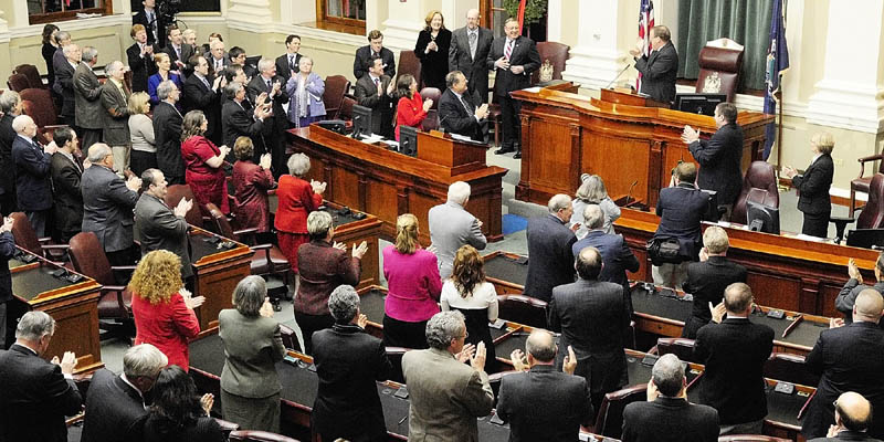 Gov. Paul LePage, third from left, back row, receives a standing ovation Tuesday night from Senate President Kevin Raye, at the podium, and legislators before giving his first State of the State address to a joint session of the Maine House and Senate at the State House in Augusta.