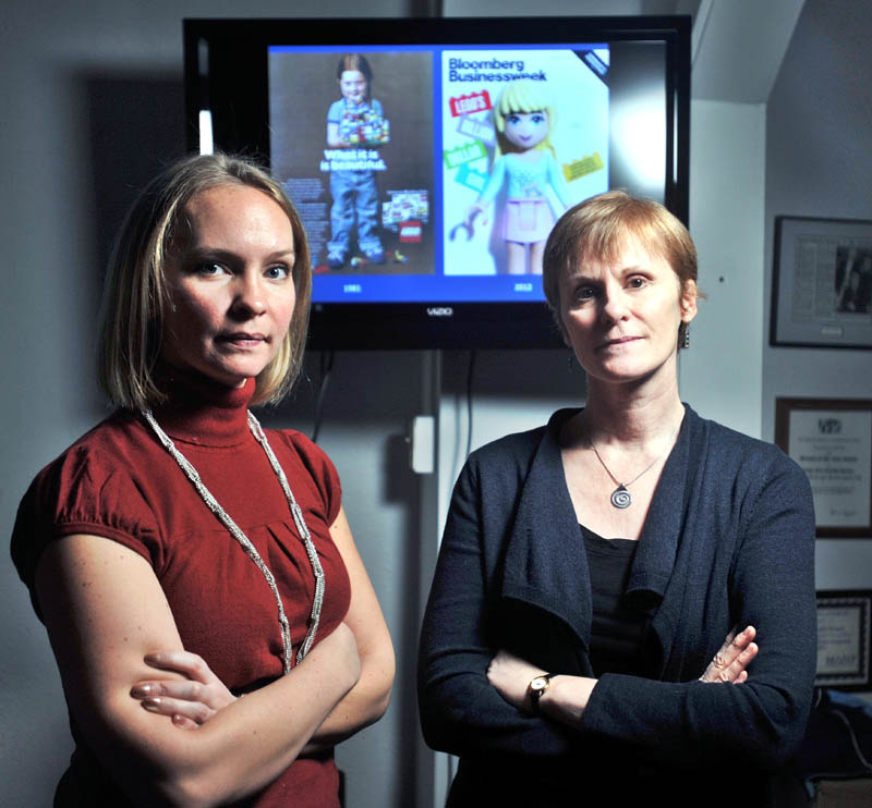 SAYING NO TO LEGO: Megan Williams, left, president of Hardy Girls Healthy Women, and Lyn Brown, a professor at Colby College, stand in front of two Lego advertisements at the Hardy Girls Healthy Women office in Waterville on Friday. The women are behind a protest of a new Lego line.