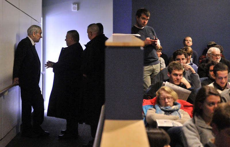 THE PLAN: Ron Paul, far left, speaks with his security advisor in the wings of Ostrove Auditorium at Colby College before speaking on Friday.