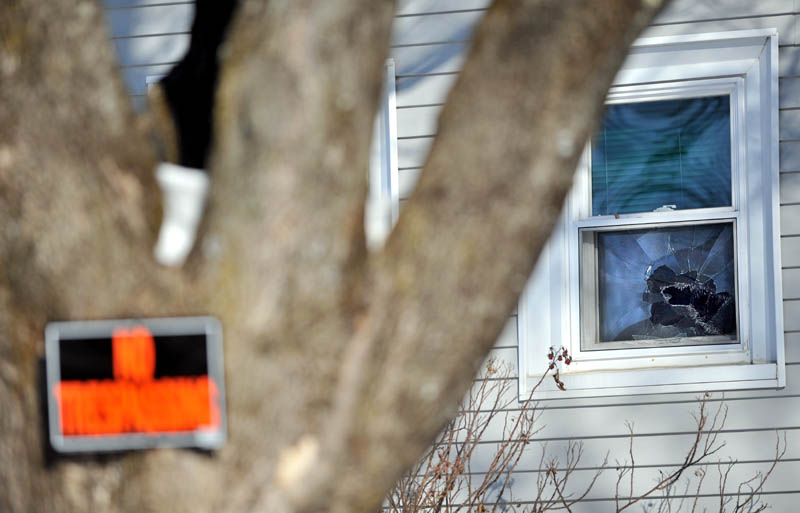 ACCESSING THE DAMAGE: A broken window in the background is one of several windows broken Friday night at Justin DePietro's residence at 29 Violette Ave.