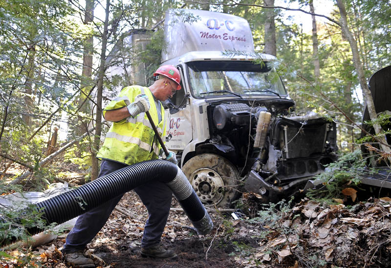CLEAN UP ACT: CleanHarbors employee Keith Wilson vacuums fuel Wednesday from a tractor trailer that went off Interstate 95 in the northbound lane in Bowdoinham and came to rest in the woods. The driver was uninjured.