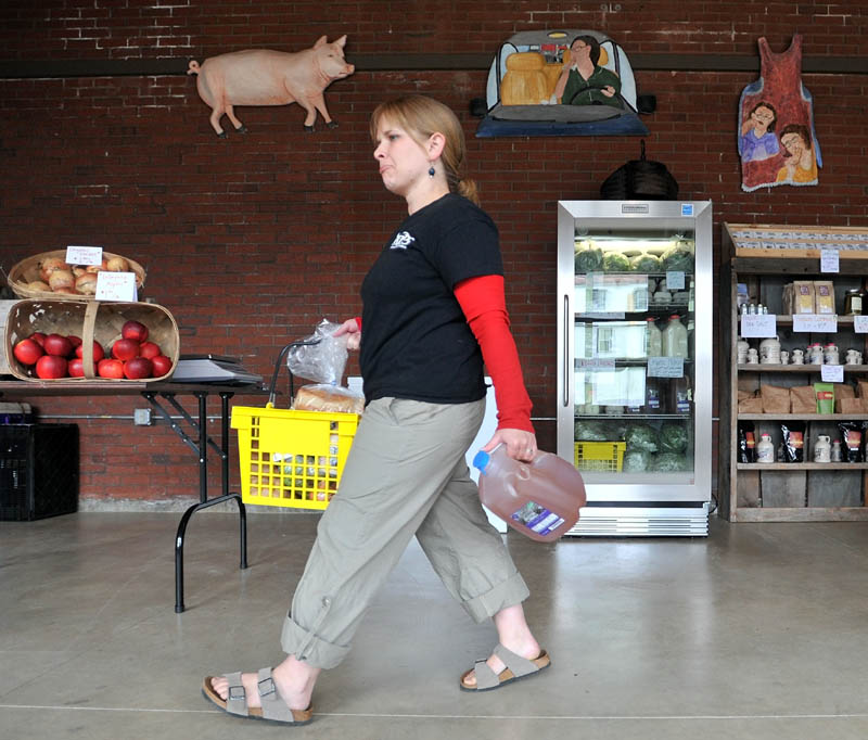 CARRYING HER SHARE: Gwynne Dunphy picks up her share of produce, milk and cider Wednesday as part of the Pickup program, a new community supported agriculture program at the Grist Mill in Skowhegan.