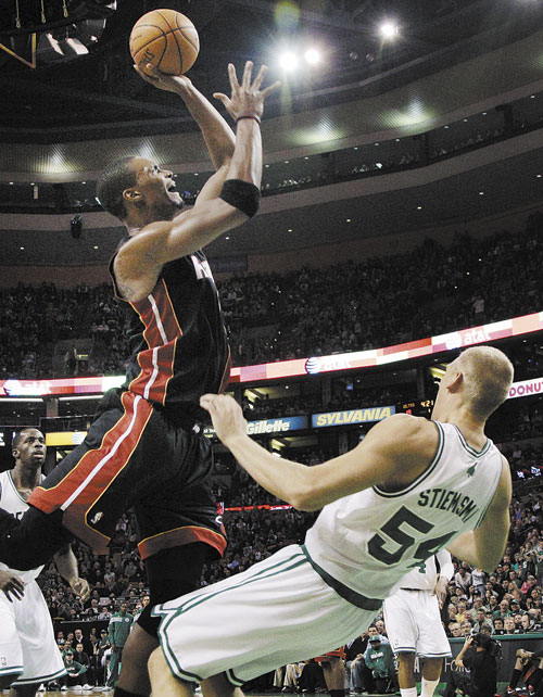 CHARGE: Boston Celtics center Greg Stiemsma (54) draws an offensive foul on Miami Heat power forward Chris Bosh in the first half Sunday in Boston.