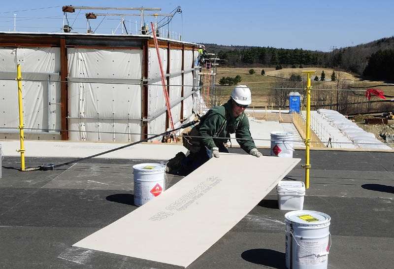 A G&E Roofing worker moves an insulation board into place last week at the new MaineGeneral regional hospital being built in Augusta.