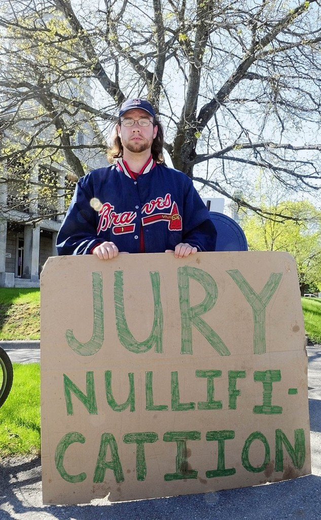 While a jury deliberates upstairs on the case of five Occupy protesters charged with trespassing at the Blaine House last November, Jarody holds a sign in front of Kennebec County Superior Court on Thursday morning in Augusta.