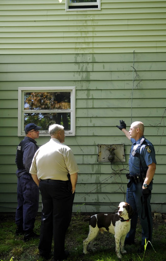 Maine State Police officer Robert Cejka, right, confers with Augusta Police Lt. Keith Brann, center, and State Police Sgt. Jeff Mills Thursday outside an apartment building that Cejka searched with his bomb sniffing dog on Gage Street in Augusta. Law enforcement officers from several agencies searched two apartment buildings on the street for explosive materials.