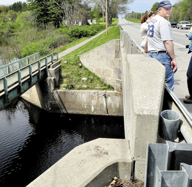 Ken Gagnon of Waterville and his daughter Bethany stand on a bridge on U.S. Route 201 in Hinckley over Martin Stream on Sunday. Police divers searched under water for his sister Cora Marley of Skowhegan, who police say went off the roadway in her vehicle Saturday evening and into the water.