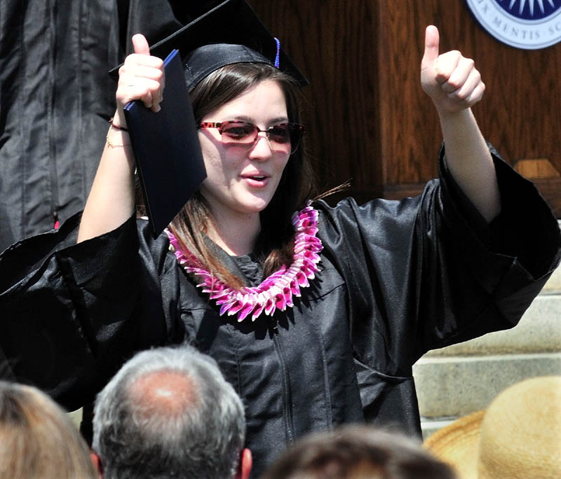 YEAH: Colby College senior Tate Kaneshige holds her diploma and gives a thumbs-up to relatives during commencement on Sunday.