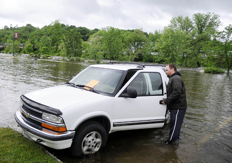 Ryan Crouse removes his truck Monday afternoon from the rising Cobbossee Stream in the arcade lot in Gardiner. City officials ordered all the vehicles in the arcade lot be removed ahead of flooding, when Crouse was at work.
