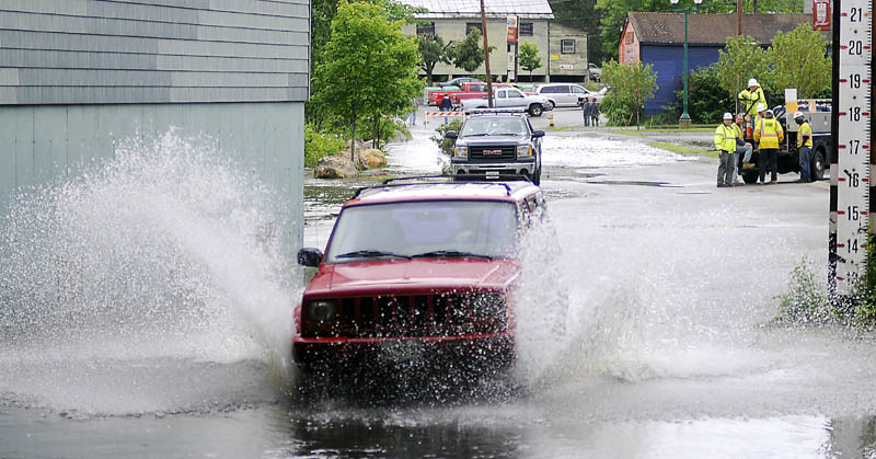 Matt LeClair drives through the flooding Cobbossee Stream in Gardiner on Monday afternoon while evacuating a friend's vehicle. The arcade lot, along Cobbossee Stream, flooded following heavy rain.