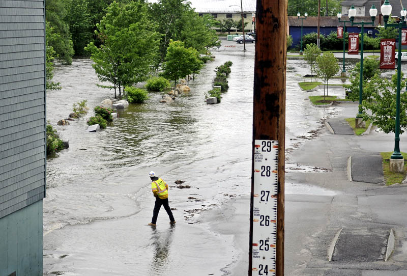A state Department of Transportation worker inspects flooding Cobbossee Stream in the arcade lot between Gardiner between Bridge Street and Maine Avenue. State crews closed bridges on both roads and city officials removed all the vehicles in the arcade lot ahead of flooding.