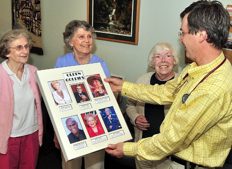 GOLDEN GIRLS: From left, Barbara Tracy, Marilyn Canavan and Betty Goulette surprise Dr. Roland Knausenberger, of Litchfield, with a poster in his office this week at Inland Medical Associates in Waterville.