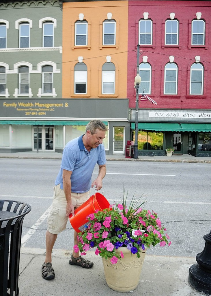 Larry Fleury waters a planter on Water Street on Thursday evening in downtown Augusta. The Augusta Downtown Alliance has installed over fifty planters and hanging baskets on the street.