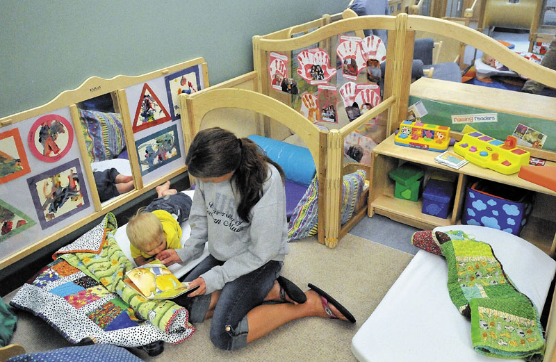 Monica Pollard reads a story to Landon Dwelley, 1, before nap time at Head Start at Educare Central Maine in Waterville on Friday.