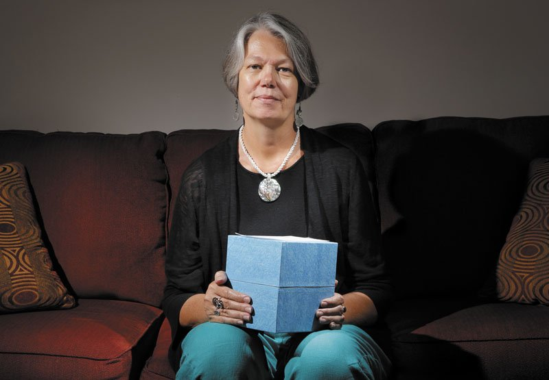 Karin Anderson holds a box of the cremated remains of her husband Steve, who passed away two and a half years ago. Anderson is photographed in her Portland apartment on Thursday.