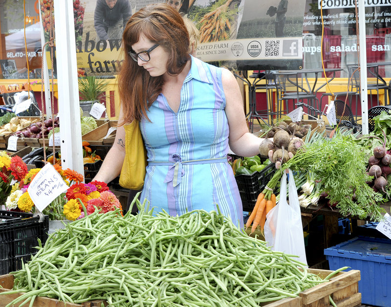 "Beth Taylor of Portland shops at the Fishbowl Farm stand Wednesday at the Portland farmers market in Monument Square. She said she tries to buy organic because she wants ""clean food"" grown mostly free of such things as pesticides and synthetic fertilizers."