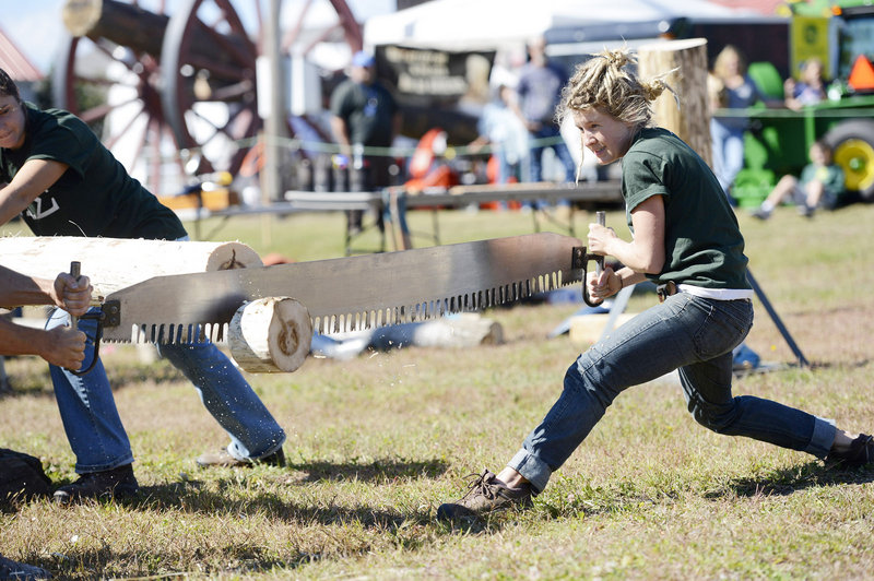 Jenny Helm of Waitsfield, Vt., works at crosscut sawing with other members of the Colby College Woodsmen's Team on Sunday at the Cumberland County Fair. Helm graduated from Colby in 2011.