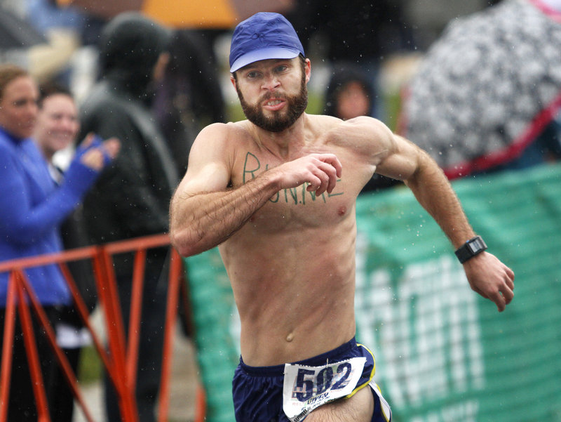 Owen Bradley of Birmingham, Ala., sprints through the raindrops Sunday to reach the finish line and complete his outing in the Maine Marathon at Portland.