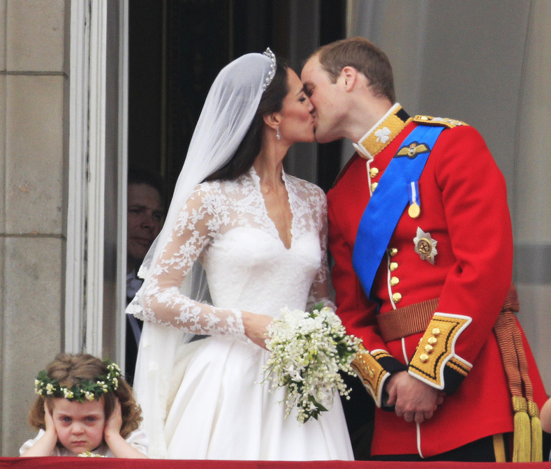 As bridesmaid Grace van Cutsem, left, covers her ears, Britain's Prince William kisses his wife Kate, Duchess of Cambridge, on the balcony of Buckingham Palace after the Royal Wedding in London Friday, April, 29, 2011.