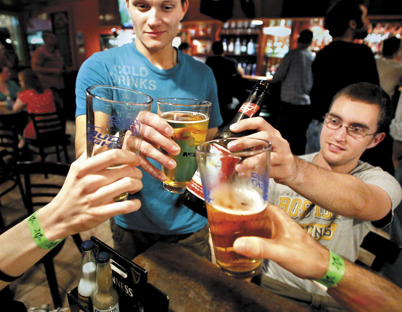 Joseph Miller, a senior ecology and environmental science major from Topsham, left, and Andy Bepuain, a senior business managment major from Bangor, toast with friends at the Bear Brew Pub in Orono.