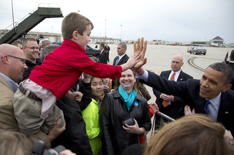 President Barack Obama high-fives a boy as he greets people on the tarmac as he arrives at Eastern Iowa Airport, Wednesday, Oct. 17, 2012, in Cedar Rapids, Iowa for a campaign stop. The president sports a pink bracelet in honor of October being breast cancer awareness month. (AP Photo/Carolyn Kaster)