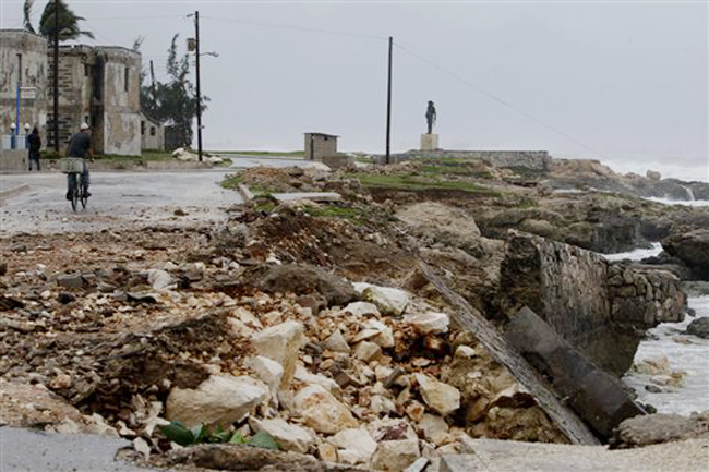 The sea wall and a road is partially damaged after the passing of Hurricane Sandy in Gibara, Cuba, Thursday, Oct. 25, 2012. Hurricane Sandy blasted across eastern Cuba on Thursday as a potent Category 2 storm and headed for the Bahamas after causing at least two deaths in the Caribbean. (AP Photo/Franklin Reyes)