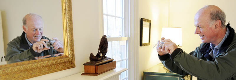 Frank Kirwin, of Braintree, MA, takes a photo of a wood carving by Ellsworth Crosby during an exhibit Sunday at the Williams House, part of the Cary Memorial Library in Wayne. The Library is exhibiting Crosby's cuts and bookplates from the collection of Elizabeth M. Hyatt.