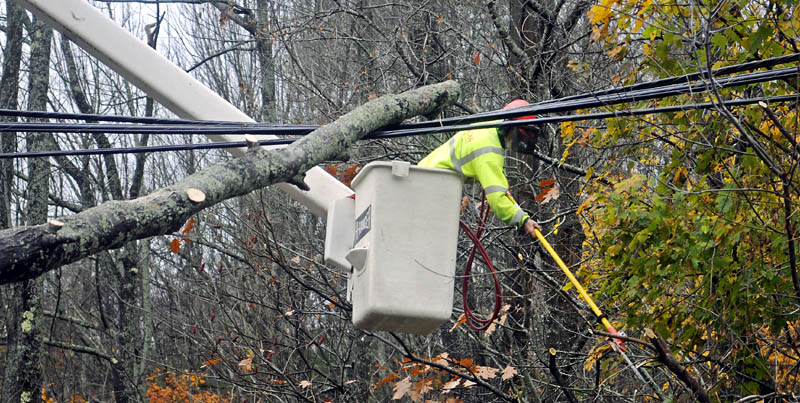 Lucas Tree employee Donny Tunison clears a limb from power lines Tuesday in Hallowell. Tunison and his colleague, Caleb Taylor, removed fallen trees as Central Maine Power crews restored power.