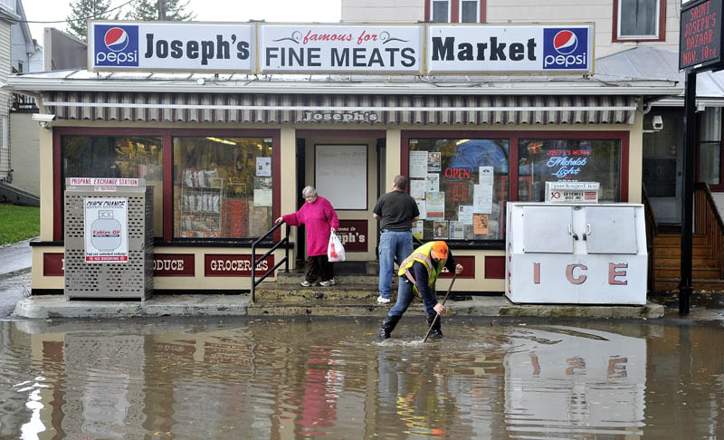 Dave Vigue of the Waterville public works department clears a clogged drain on a flooded Front Street, in front of Joseph's Market, in Waterville after heavy rain on Tuesday.