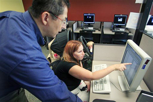 Deanna Aguilera, 30, of Salt Lake City, right, receives assistance from employment counselor Frank Trivino while job searching recently at Workforce Services in Salt Lake City.