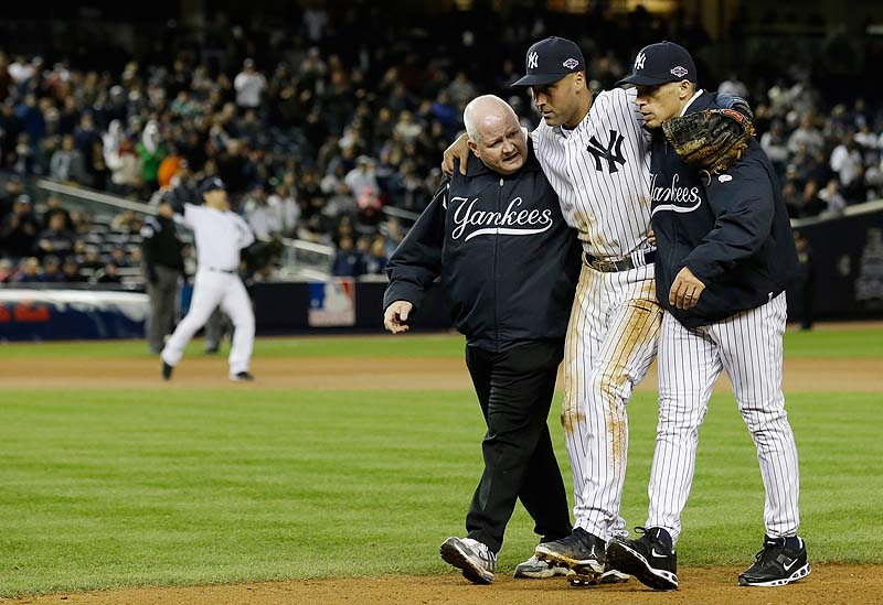 Trainer Steve Donohue, left, and Yankees Manager Joe Girardi help Derek Jeter off the field after he injured himself during Game 1 of the ALCS Saturday night against the Detroit Tigers. Jeter broke his ankle fielding a grounder in the 12th inning and is done for the postseason.