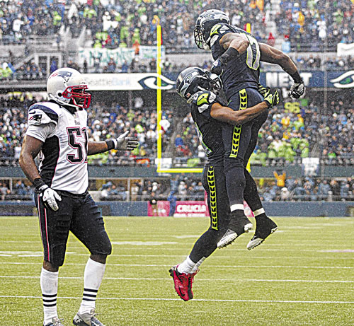 JUMP FOR JOY: Seattle's Braylon Edwards, right, celebrates with teammateGolden Tate as New England's Jerod Mayo looks on after Edwards caught a pass for a touchdown in the second half Sunday in Seattle.