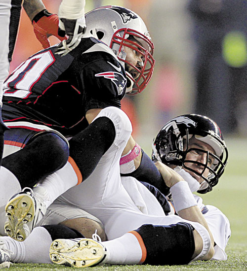TAKING HIM DOWN: Denver Broncos quarterback Peyton Manning, right, watches his fumble after being sacked by New England Patriots defensive end Rob Ninkovich in the third quarter Sunday in Foxborough, Mass.