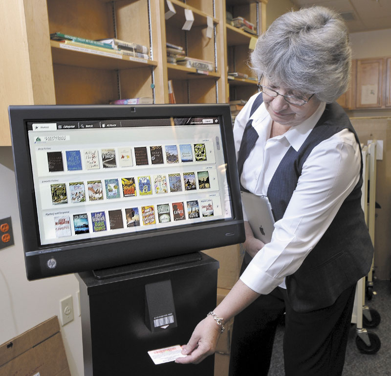 Susan Winch, assistant director of the Scarborough Public Library, demonstrates on Tuesday the Discovery Terminal patrons will use to order e-books. She scans her special-coded library card, but manual input of the numerical code will be accepted as well.