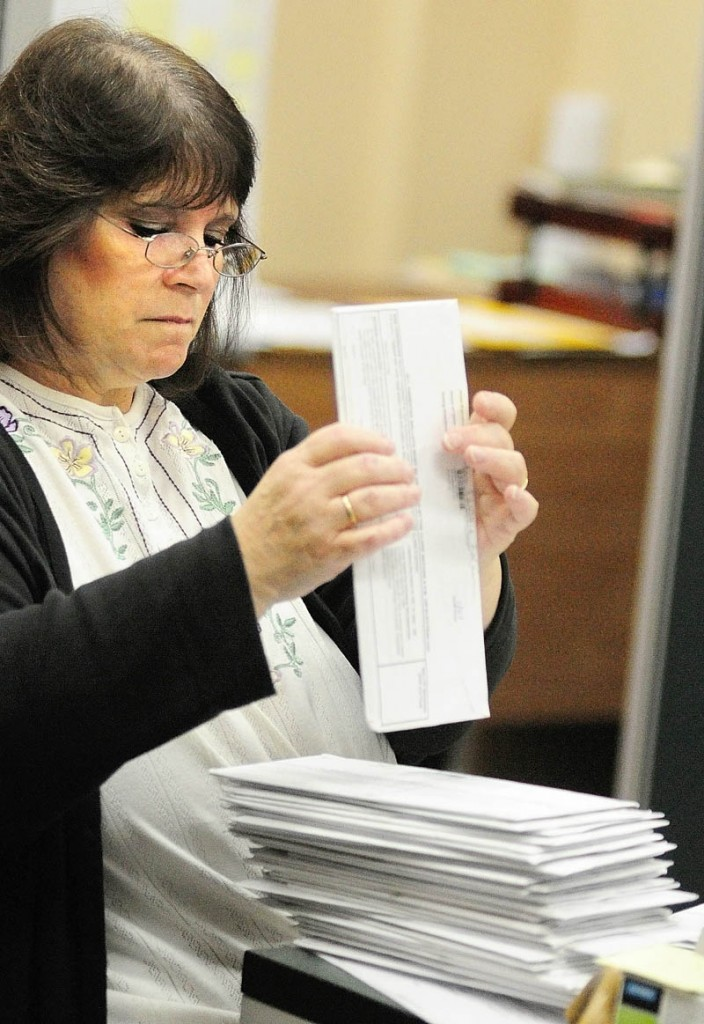 Martha Burns stacks and date stamps a stack of absentee ballots that were mailed into the city clerk's office on Thursday morning in Augusta City Center.