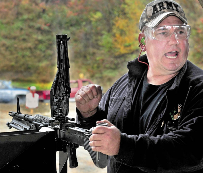 Andy Williams calls for more ammunition while reloading an automatic weapon during the Maine Wounded Warrior Shoot Out that his family hosted for injured veterans in Anson, on Sunday.