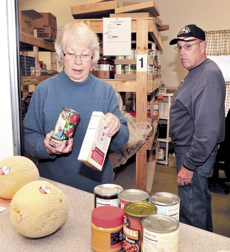 Volunteer Betty Lou Jones fills a request at the Greater Waterville Area Food Pantry in Waterville on Wednesday. Jones is leaving the organization after serving since it was started. At right is volunteer Ken Libby.