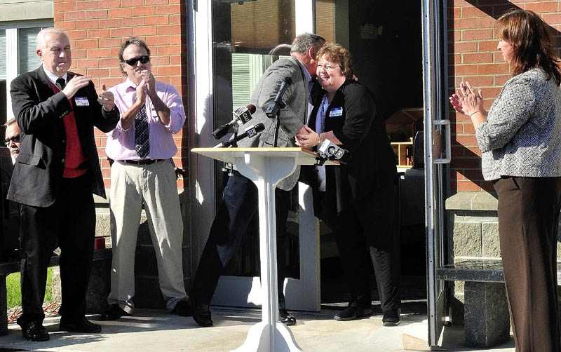 Gov. Paul LePage congratulates Mid-Maine Homeless Shelter Executive Director Betty Palmer as Doug Cutchin, left, Kevin Joseph and Susan Reisert applaud during the opening of the new shelter on Monday.