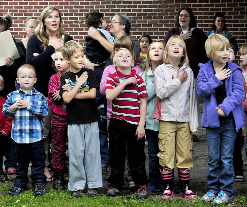 Staff photo by David Leaming CHARTER SALUTE: Children salute the American flag that was raised for the last time before being retired during the opening of the new Cornville Regional Charter School on Monday.